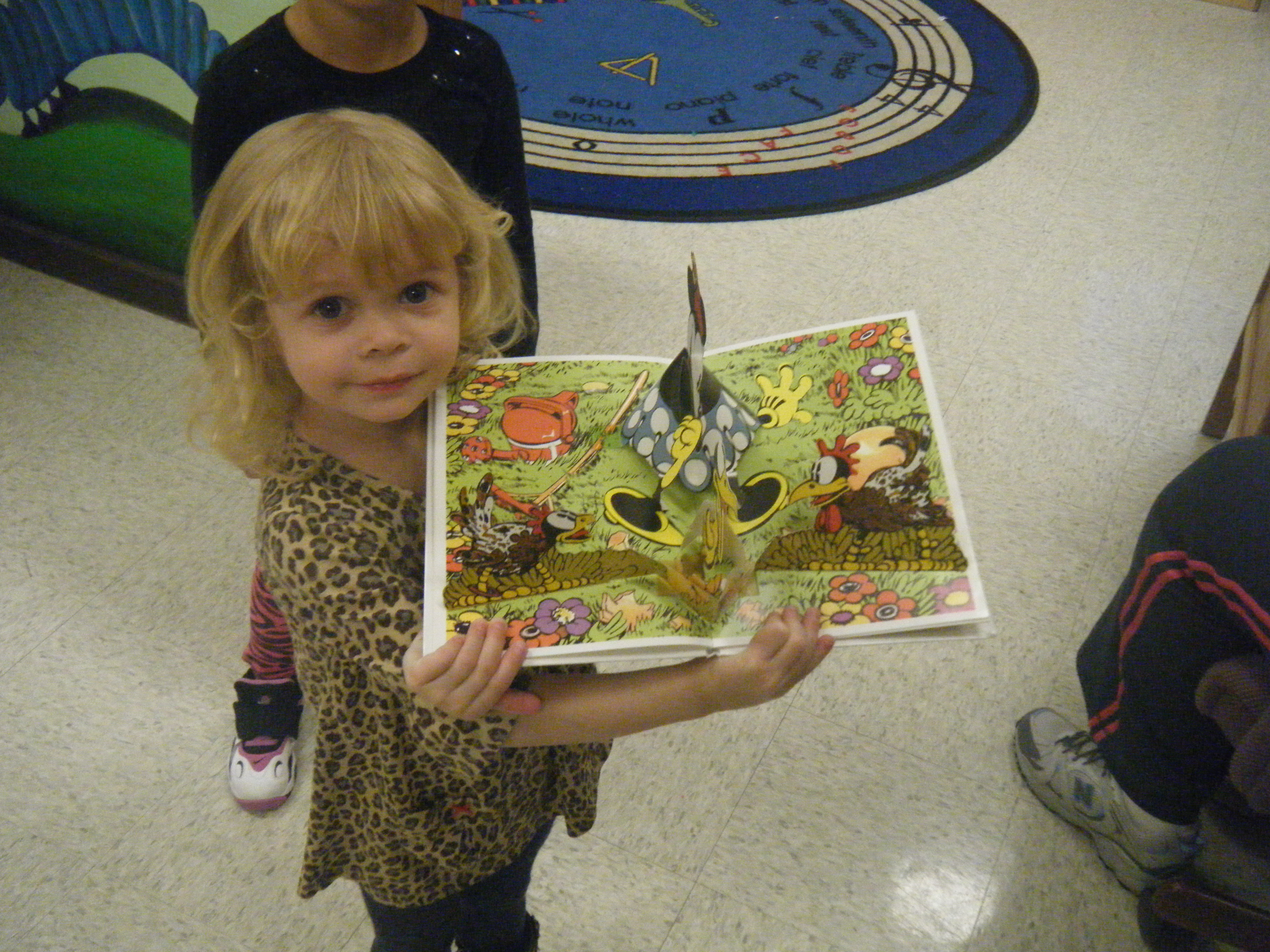 A young girl is proud to read a popup book.